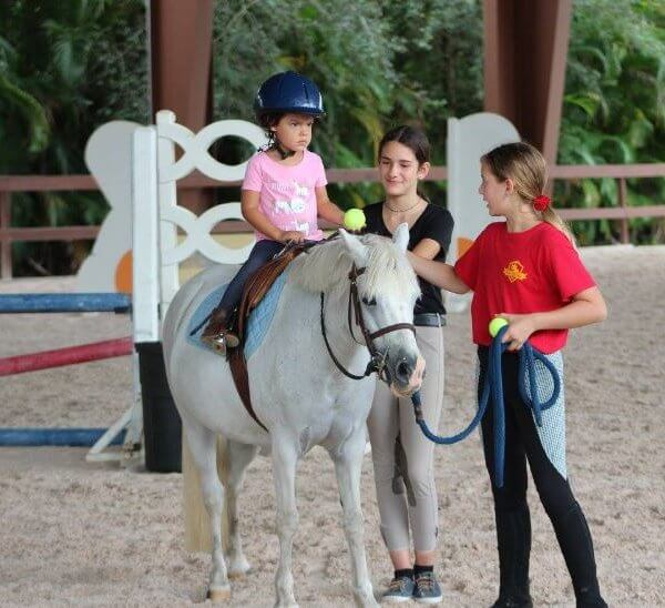 Little kid riding a pony with the help of a camp counselor