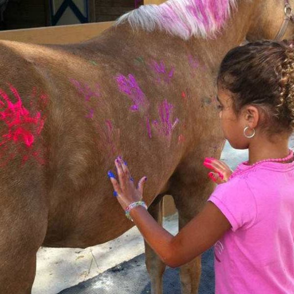 Kid hand painting with horse