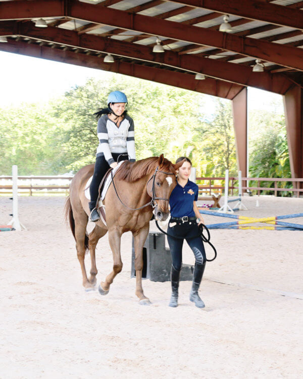 Trainer giving lady riding lessons