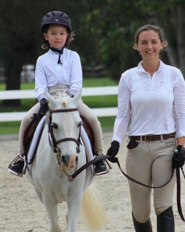 Trainer giving child horse riding lessons